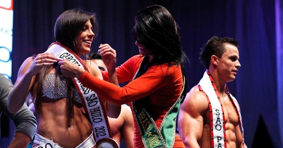 Nathalia recebe a faixa das mãos de Marissol Dias, a Garota Fitness Brasil 2012