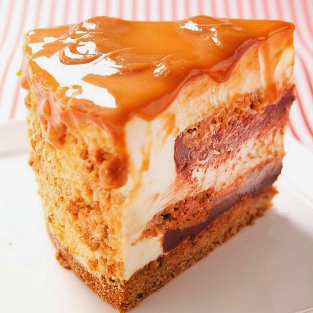 A foto é de uma fatia de torta assinada pelo Chef Lucas Corazza, intercalada por camadas de: cheesecake leve, feito sem assar, cookies e ganache, coberto por um fino e reluzente doce de leite que escorre na beirada da fatia.