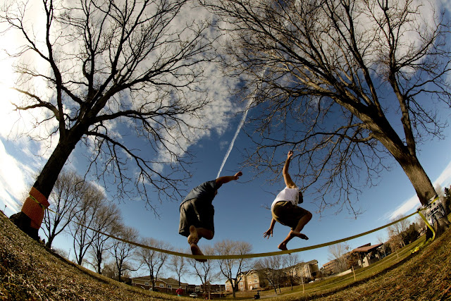 Two guys getting thrown off of a Gibbon Slackline in a park near Golden, Colorado.