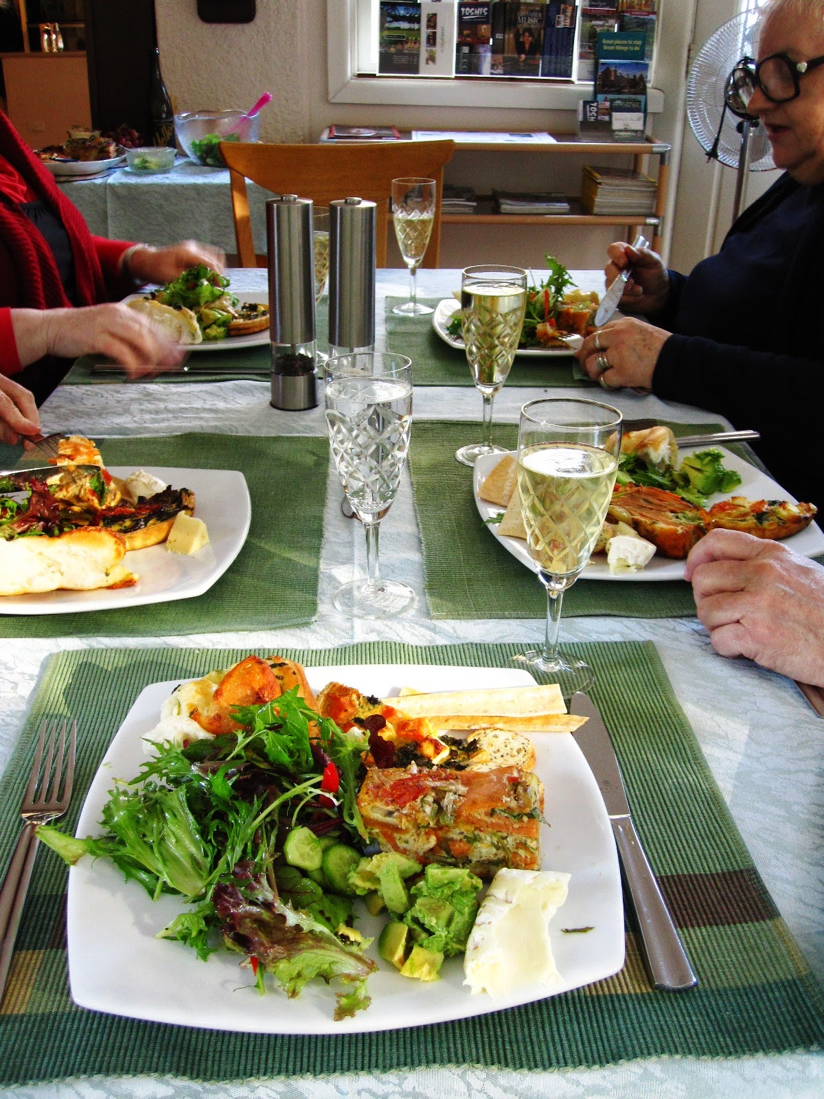 Table with five people eating lunch with glasses of sparkling wine.