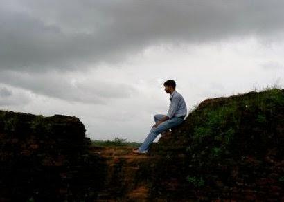 [uomo che sta seduto su uno scoglio e prova sentimenti per qualcosa]