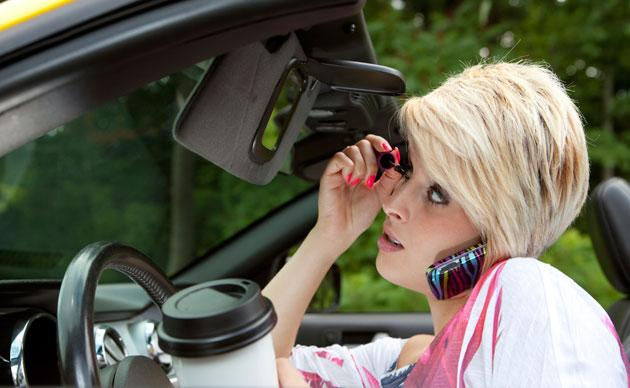 Woman drives while applying makeup driving coffee and talking on phone