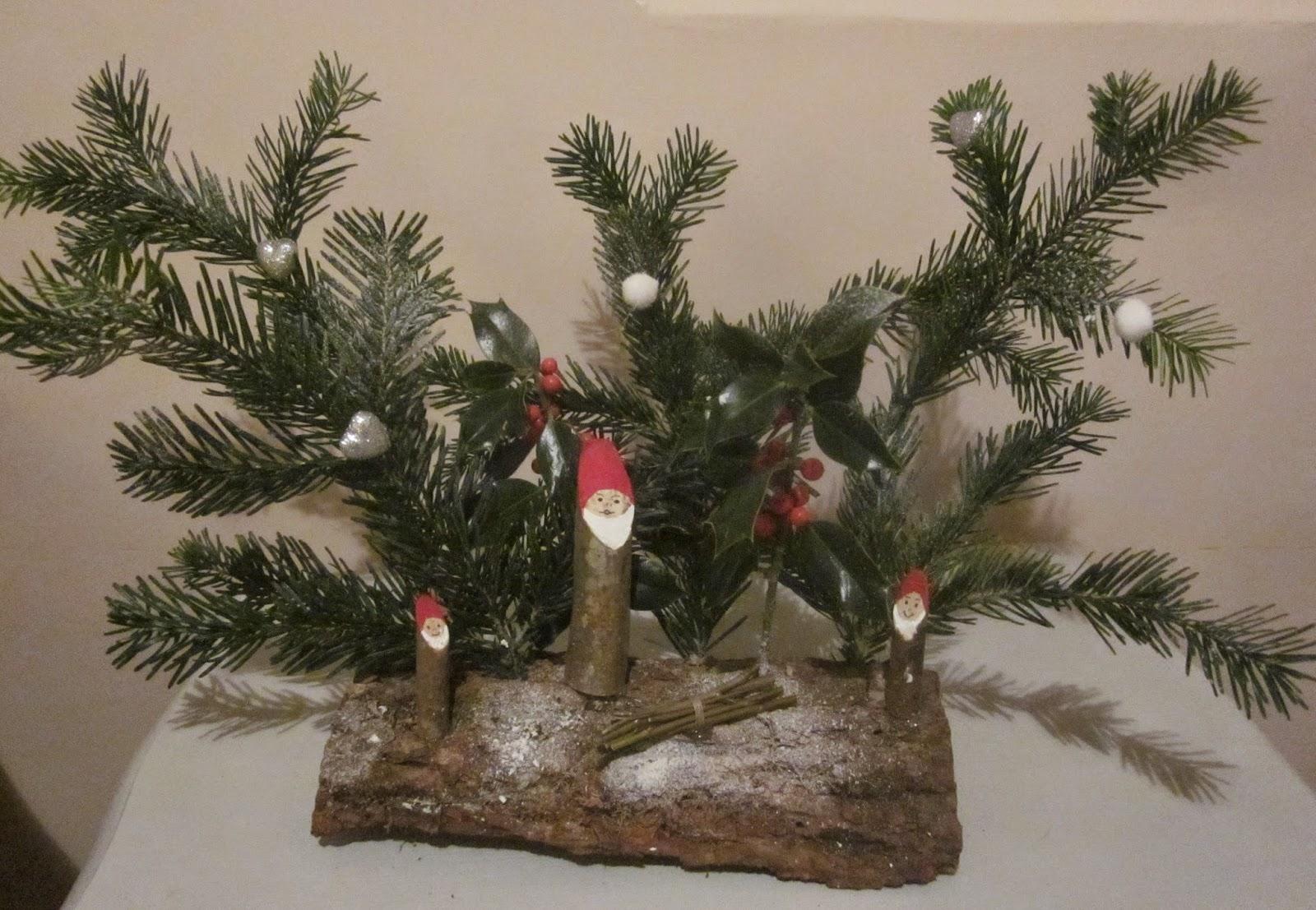 Avec une perceuse, faire des trous dans la buche pour planter les branches  de sapin et de houx. Avec un pistolet à colle coller les lutins ou Père Noël