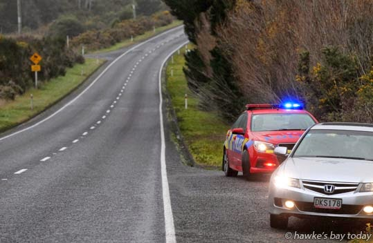 Red police car stops a motorist on SH5 in Queen's Birthday Weekend holiday traffic photograph
