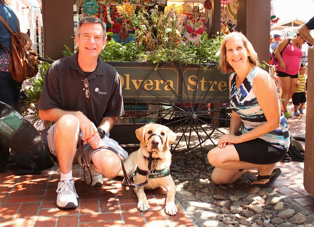 Two puppy raisers kneel down posing with their yellow Lab guide dog puppy.