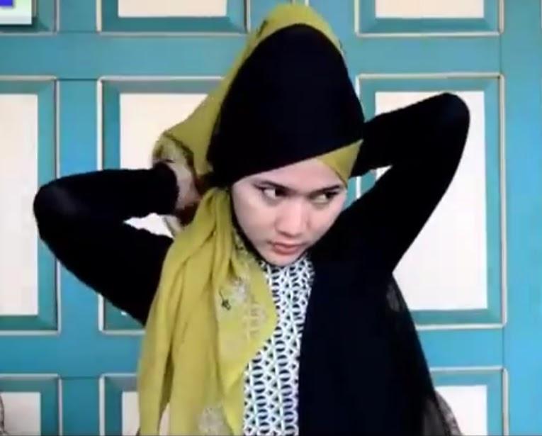 Sisa jilbab warna hitam di tarik kebelakang dan dilewatkan kebagian