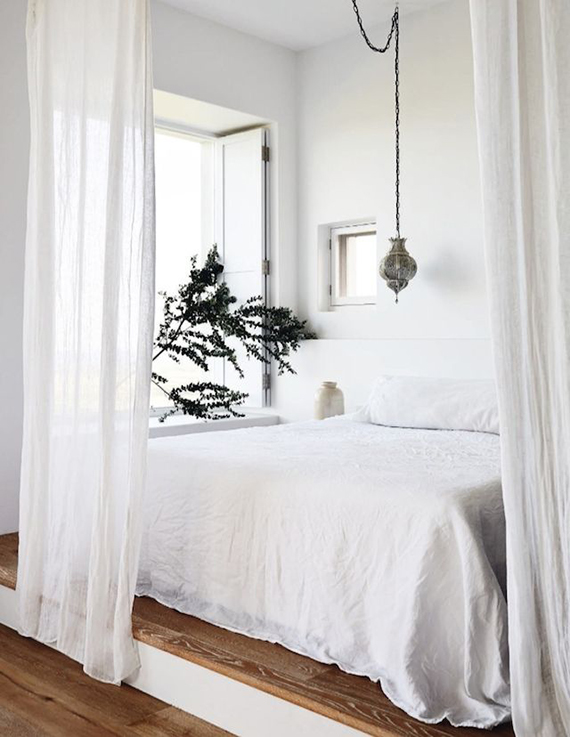 Cozy bed behind sheer curtains