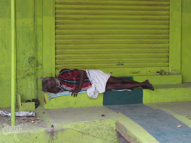 man sleeping in front of his shop