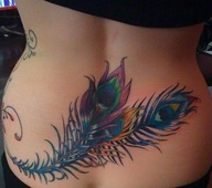 Peacock feather tattoo on lower back