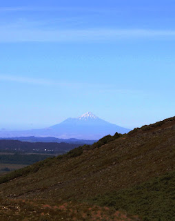 Image of a snowcapped, perfected pointed, mountain in the distance.