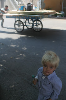 Anton with a blue lollipop and men pushing a cart in the background.