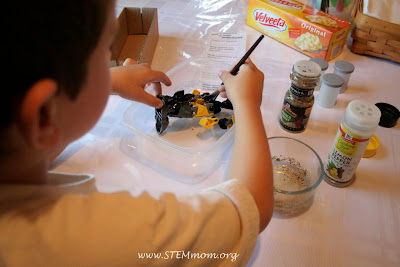 Boy pretending to put oil and spices on his mummy: STEMmom.org
