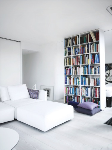 Floor to ceiling bookshelf stuffed with books dividing a small, white room with purple pillows in two