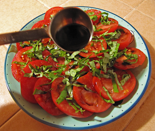Hand with Tablespoon Sprinkling Balsamic on Tomatoes