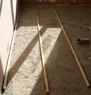 The first lengths of wood, screwed into the floor