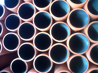 A stack of brick-red pipes seen from the end