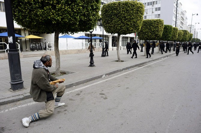 Тунисец целится в полицейских…из багета во время революции в Тунисе в 2010-2011 гг.