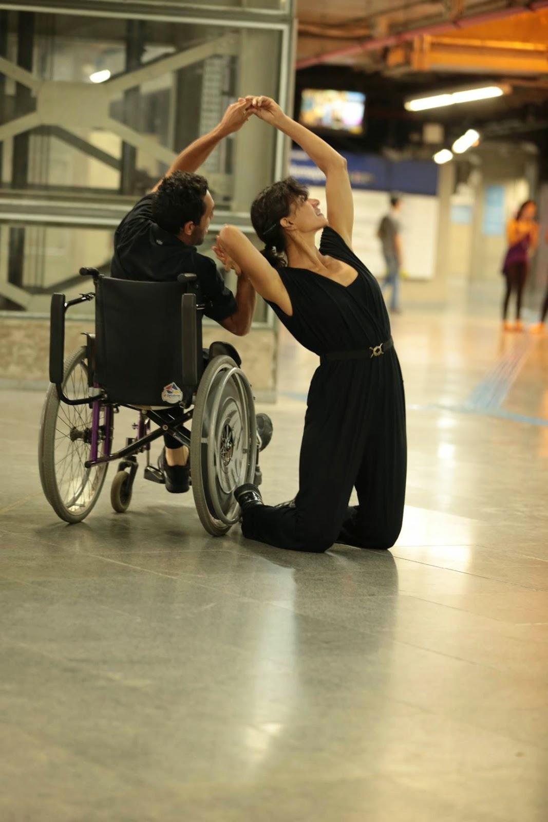 Descrição da Foto: Dois intérpretes vestidos de preto dançam na plataforma do metrô. Um deles está numa cadeira-de-rodas. A outra está ajoelhada, rosto voltado para cima, de costas para o cadeirante. Estão de mãos dadas.  Pessoas passam, elevador no fundo.
