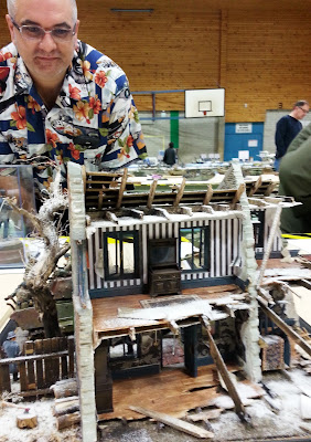 A man looking at a model bombed-out building diorama at a scale model exhibition.