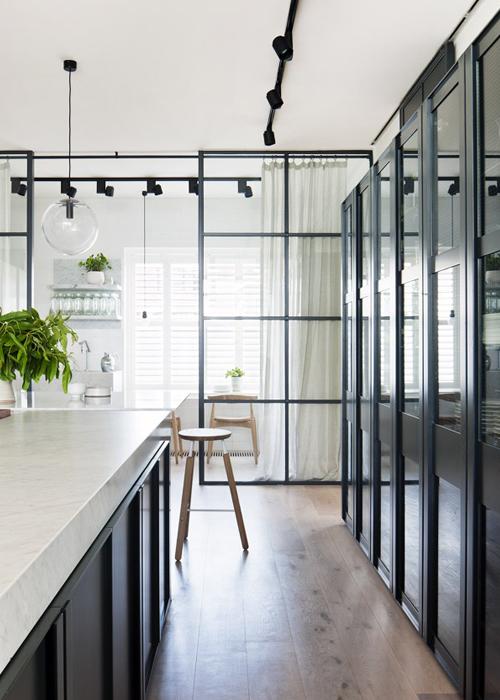 cocina en negro con encimera de mrmol y pared de puertas correderas de cristal y marco de hierro negro black kichen with marble bench top and black metal