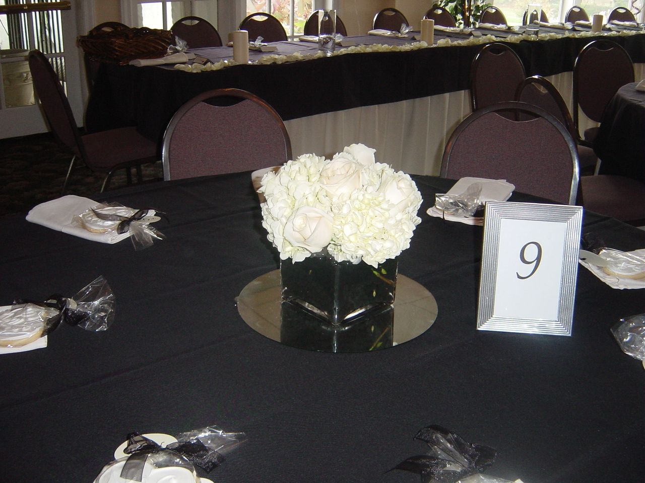 Whimsical welcomes floral design february 2013 half of the tables had low glass square vases holding white hydrangea and ivory roses on a bed of black bubbles reviewsmspy
