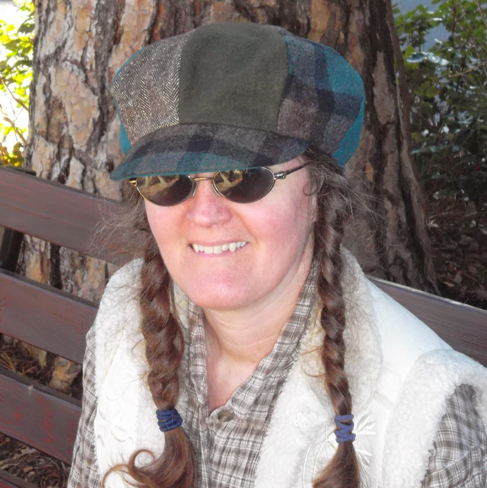 Cynthia M. Parkhill wearing eight-paneled newsboy style brimmed hat. From left to right, in order, panels are fully or partially visible in teal, brown houndstooth, dark green, brown plaid and teal. The brown houndstooth and dark-green panels occupy center front of the hat, above a bill of brown-and-green plaid. A thin outline of the bill's teal underbill is just visible along the bill's front edge.
