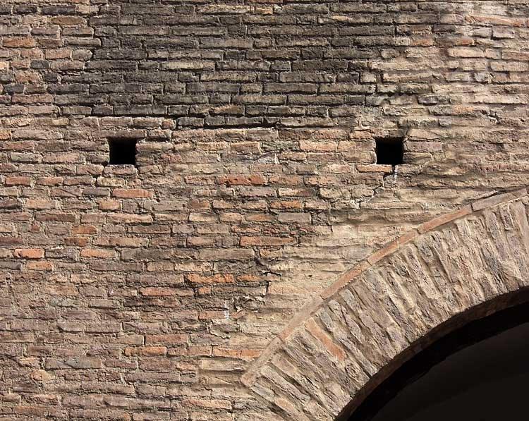 Parede de tijolo maciço com duas aberturas ao meio e um pedaço de arco no canto inferior esquerdo