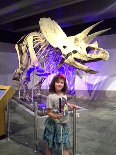 girl with cane in front of a Triceratops