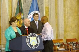 Herbert (derecha) es felicitado por la Directora de Distrito de USCIS en Washington, DC, Sarah Taylor (izquierda), el Director de USCIS, Alejandro Mayorkas (al centro a la izquierda) y el Secretario del Tesoro, Jack Lew (al centro a la derecha)