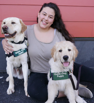 Delphine smiles while posing with a yellow Lab guide dog puppy and a Golden Retriever guide dog puppy.