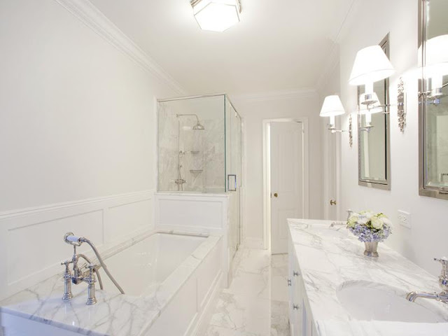 master bathroom with marble drop in tub and counter tops and a clear glass enclosed shower