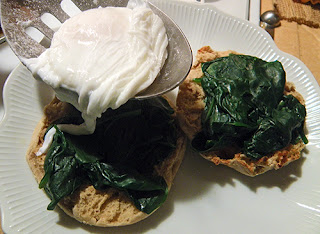 Poached Egg Being Scooped onto Spinach and Muffin
