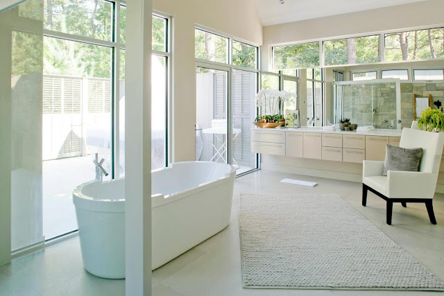 Master bathroom in a modern farmhouse with a stand alone tub, large windows and neutral cabinets