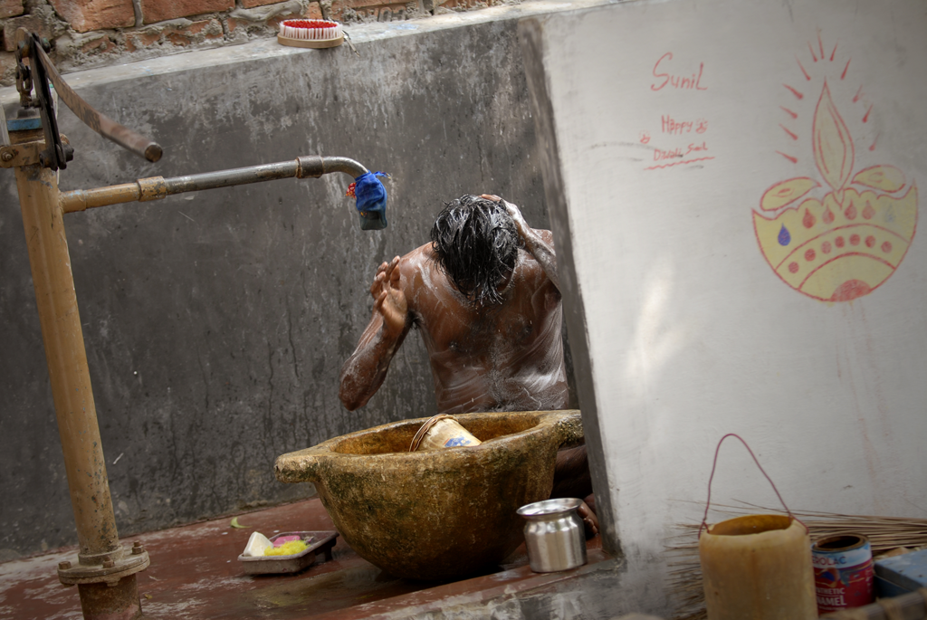 This is an India photo of a man bathing near his home in the village