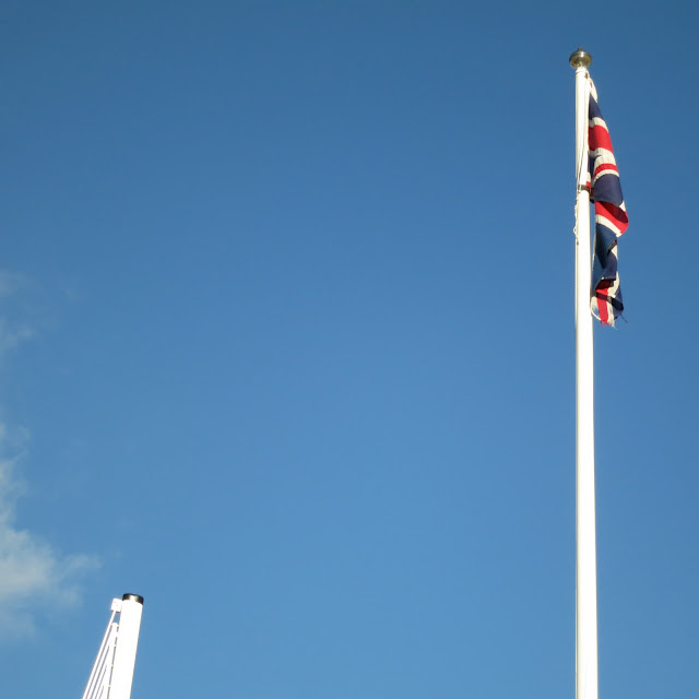 Top of raised barrier and part of top of flag pole with Union Jack against a blue sky.