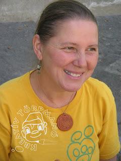 Sárga rövidujjú polóban hátrafogott hajú mosolygó szemű asszony.