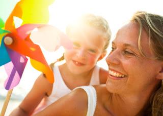 Madre e hija jugando con un molino de viento