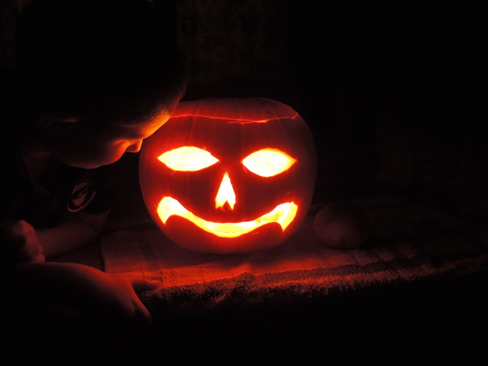 carved pumpkin for halloween with face and 3 candles inside