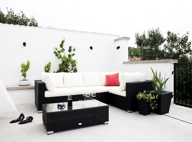 white outdoor patio with black potted plant, coffee table and sofa with white cushions and a view of a backyard
