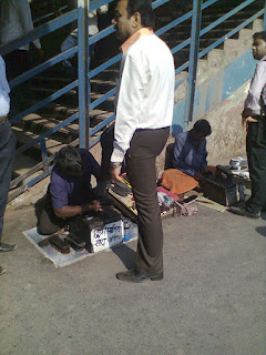 Shoe shine man polishing shoes at railway station, andheri bandra cst central railway shoe polishers