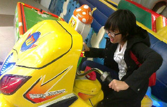 Ghaida JKT48 sedang menaiki permainan anak kecil