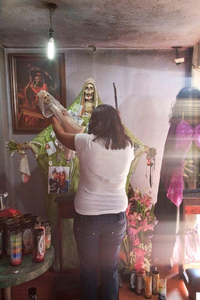 hechicera ante el altar de la santa muerte, le ofrece una figura de bebe esqueleto vestido de blanco