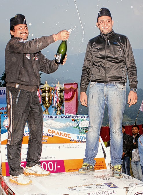 Subir Roy and Nirav Mehta, members of the team which came first in the rally, open a bottle of champagne to celebrate their victory