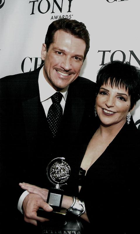 Szot photographed holding his tony award next to presenter liza