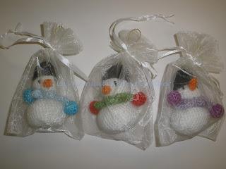Muñequitos de nieve hechos a crochet para el árbol de Navidad envueltos en bolsitas de organza