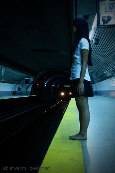 Japansk pige på perron-kanten til metro