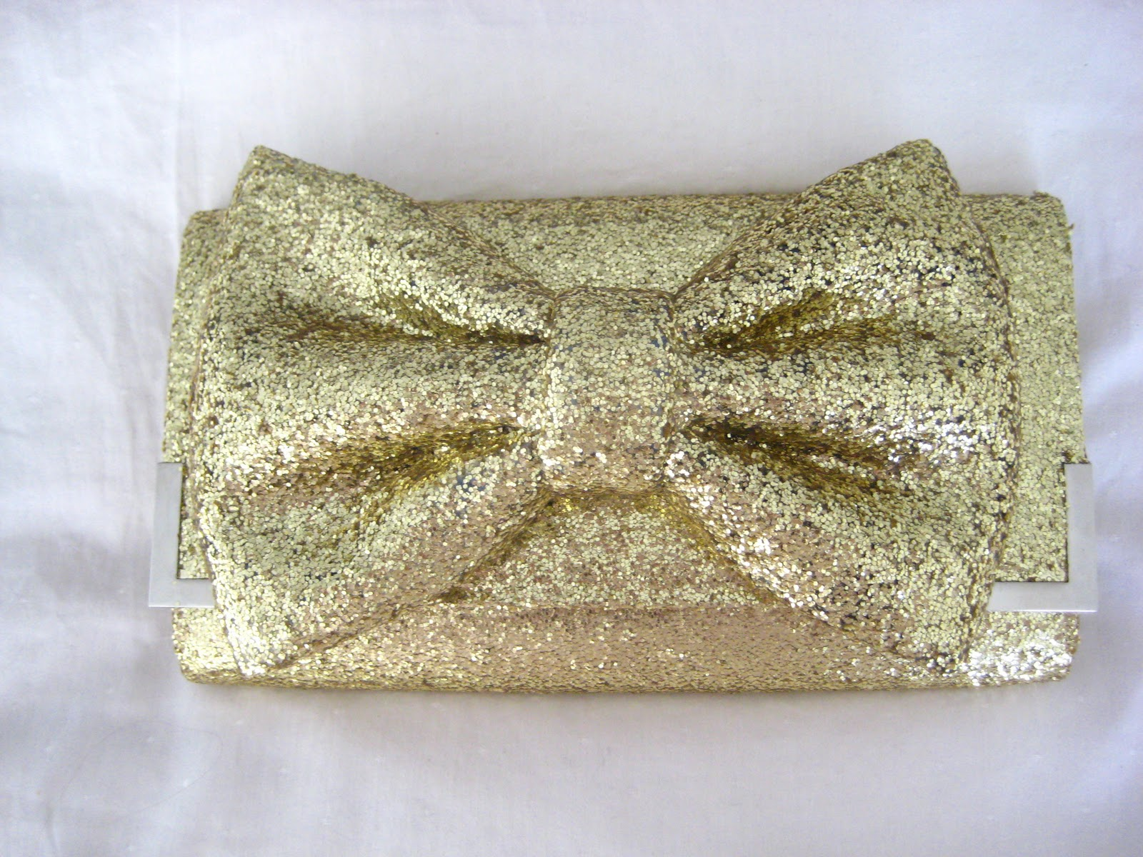 The World is My OysterMake ItGlittery Gold Bow Clutch