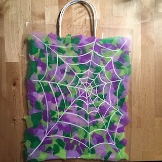 Trick or treat bag made with shades of purple and green tissue paper with a white painted spider web