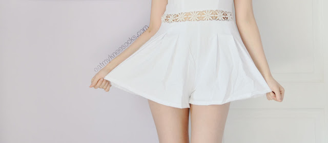 Close-up of the flared hem on the white crochet-detailed romper from Fanewant on Storenvy.