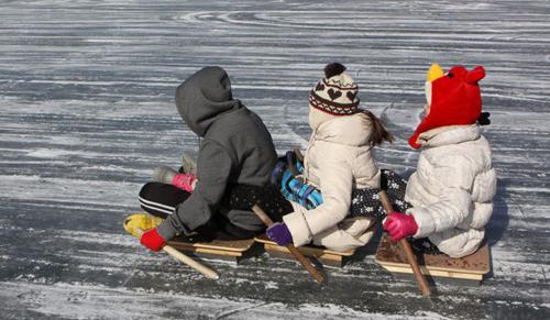 Niños coreanos jugando con un trineo tradicional